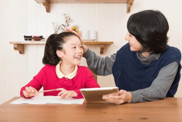 勉強しているところを母親に褒められ嬉しそうな子ども